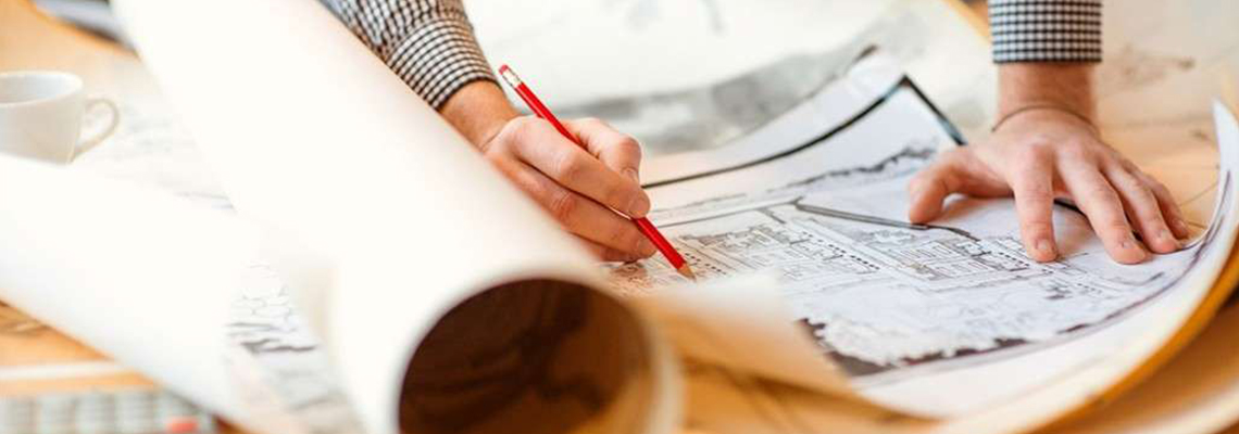 Employee leaning over architectural drawings holding a pencil to make notes